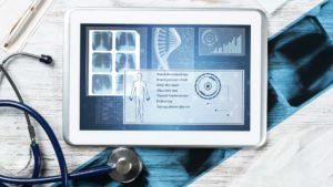 Human genetic research in medical laboratory. Tablet computer with DNA helix structure on screen. Stethoscope, x-ray image and cardiogram on wooden desk. Medical diagnostics and patient genome testing